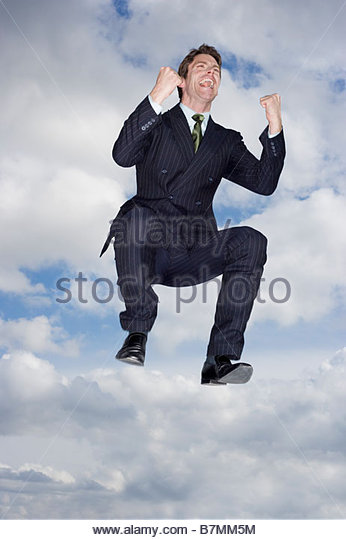 A businessman making victory gesture, leaping in the air - Stock Image