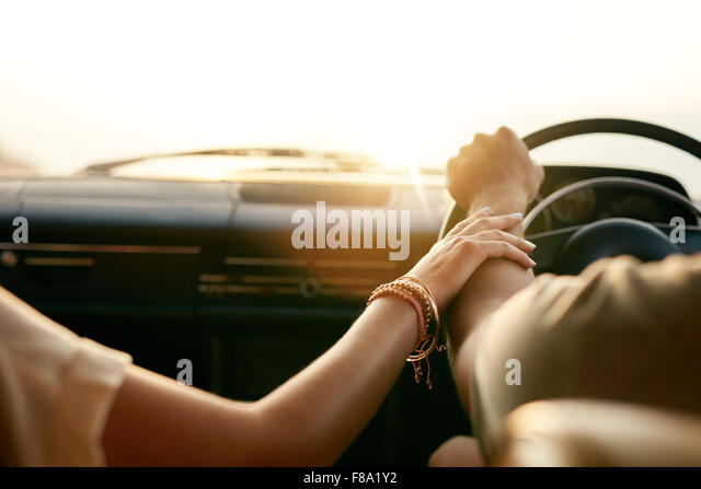 Rear view of a young couple holding hands while sitting in their car together. Man and woman on a road trip. - Stock-Bilder