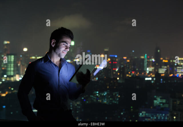 Young businessman looking at digital tablet in front of skyscraper office window at night, Shanghai, China - Stock-Bilder