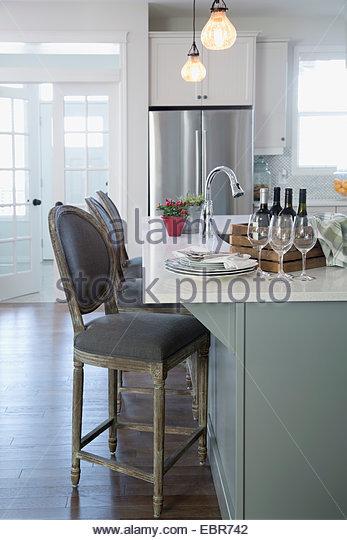 Wine bottles and glasses on breakfast bar - Stock Image