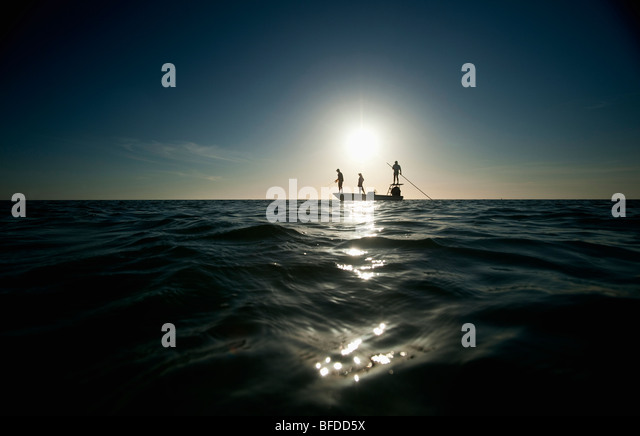 A couple fish as a man pilots a small boat in Florida. (silhouette) - Stock Image