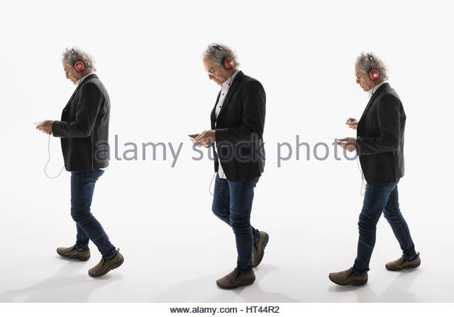 Sequence senior businessman listening to music with headphones and mp3 player against white background - Stock-Bilder