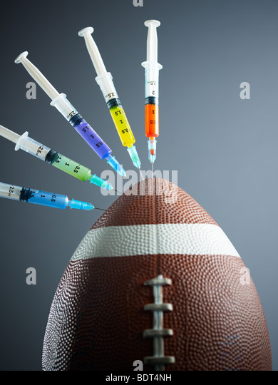 five syringes threaded in american football ball. Copy space - Stock Image