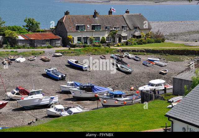 View of thatched cottages and boats at Porlock Weir, with tide out,Somerset,UK - Stock Image