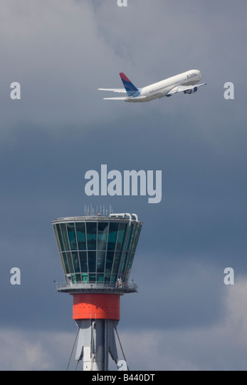Delta Air Lines Boeing 767-332/ER taking off in the background of London Heathrow control tower. - Stock Image