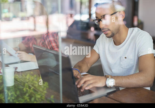 Man using laptop in cafe - Stock-Bilder