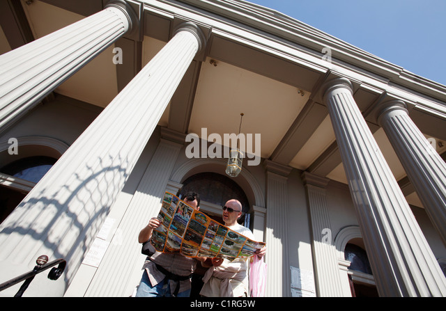 Two tourists read a map on the steps of the Catedral Metropolitana, San Jose, Costa Rica - Stock Image