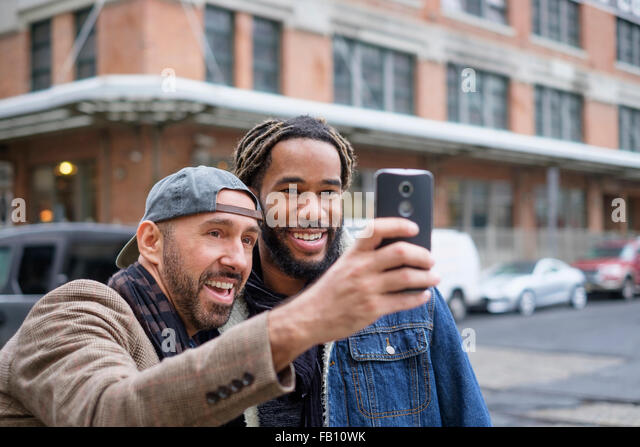 Smiley homosexual couple taking selfie with smart phone in street - Stock Image