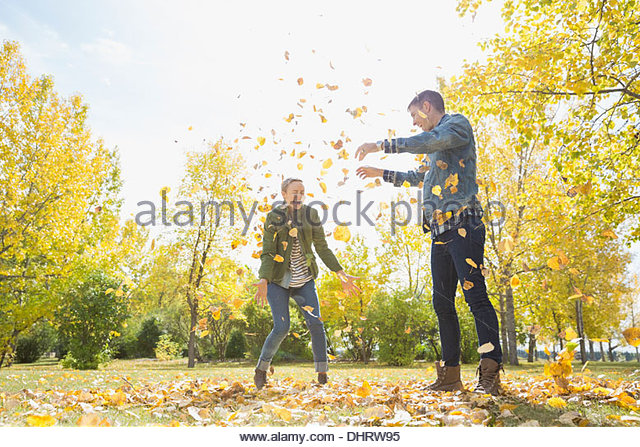 Couple playing with autumn leaves in park - Stock Image