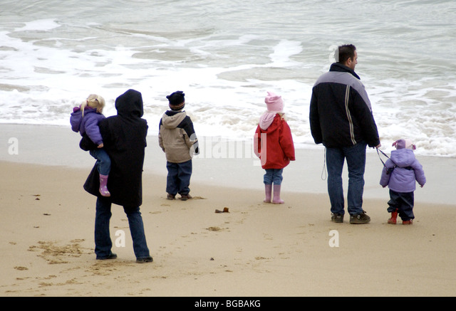 family on beach looking out to sea - Stock-Bilder