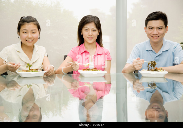 Portrait of three office workers having lunch and smiling - Stock-Bilder