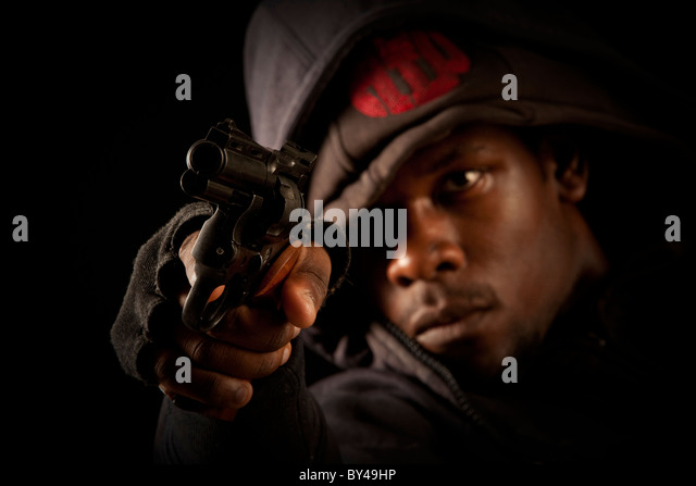 Young black male model posing with a gun - Stock Image