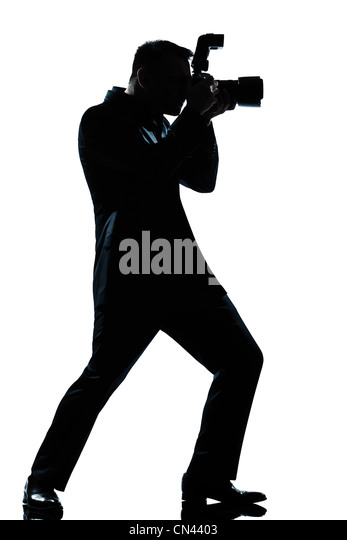 one caucasian man photographer full length silhouette in studio isolated white background - Stock Image