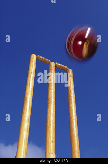 Close up of red cricket ball about to strike the stumps set against a blue sky - Stock Image