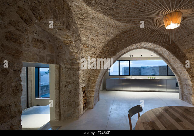 Modern rustic .Exposed stone arch and minimalist kitchen with uncurtained windows in  House, Jaffa, Tel Aviv, Israel - Stock Image