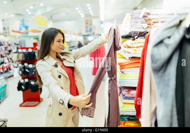 Beautiful woman glancing through clothes - Stock Image