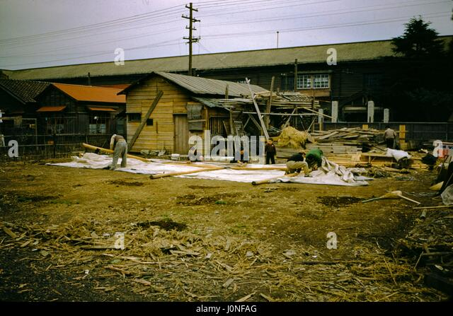 A large group of people, including several children, work to construction a home using traditional building materials, - Stock Image