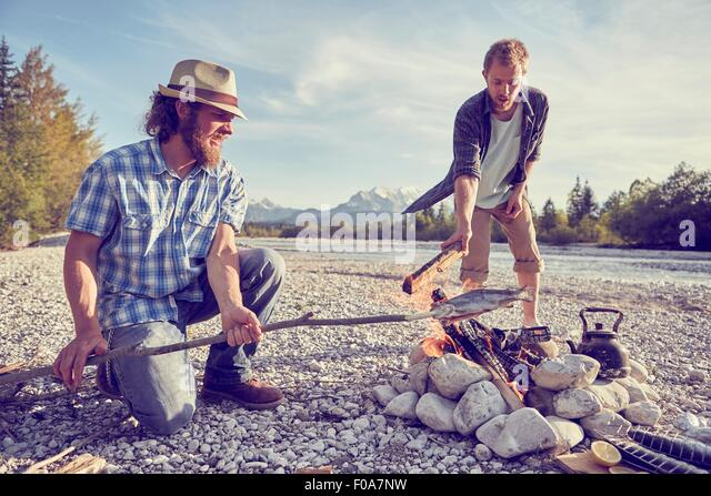 Adult men cooking fish attached to branch over campfire, Wallgau, Bavaria, Germany - Stock Image