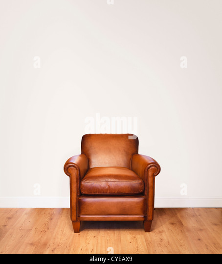 Leather armchair on a wooden floor against a white background with lots of space for copy.  The wall has a clipping - Stock Image