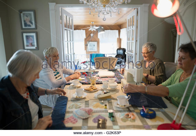 Senior women quilting at table - Stock Image