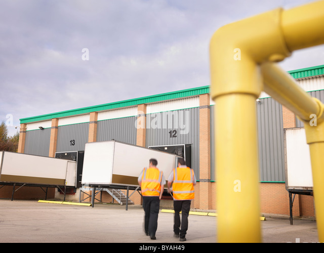 Workers with containers in loading bay - Stock Image