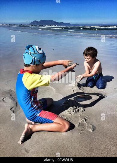 Boys playing on the beach in Cape Town, Table Mountain visible behind them. - Stock Image
