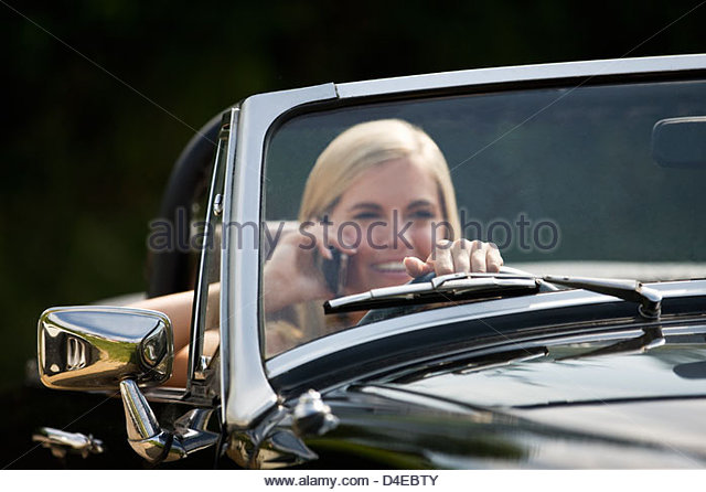 A young woman driving a black sports car holding a mobile phone - Stock Image
