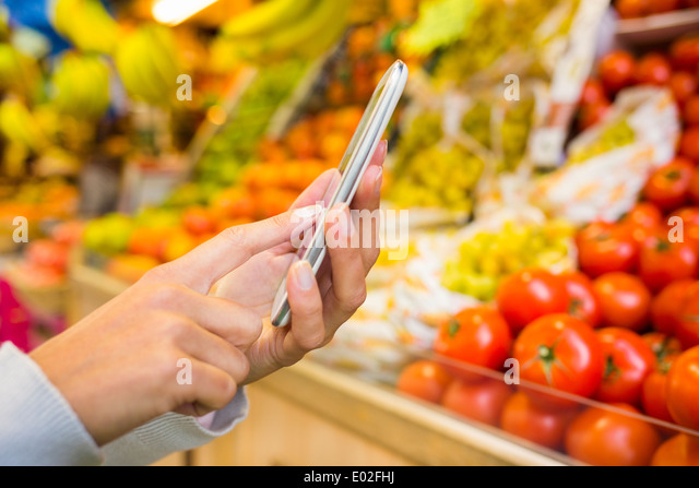 Female colse-up cell phone hand store - Stock Image