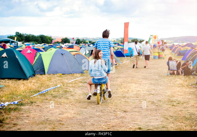 Teenage couple riding bike together at summer music festival - Stock Image