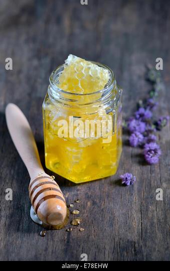 honeycomb and honey in glass jars , stiil life - Stock Image