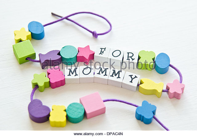 Colorful wooden toy beads in different shapes with letters that spell 'For mommy' strung together with cord - Stock Image
