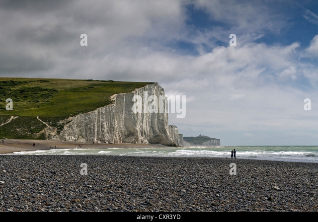 Lovers on the beach in front of Seven Sisters chalk cliffs at Cuckmere Haven, East Sussex, England - Stock Image