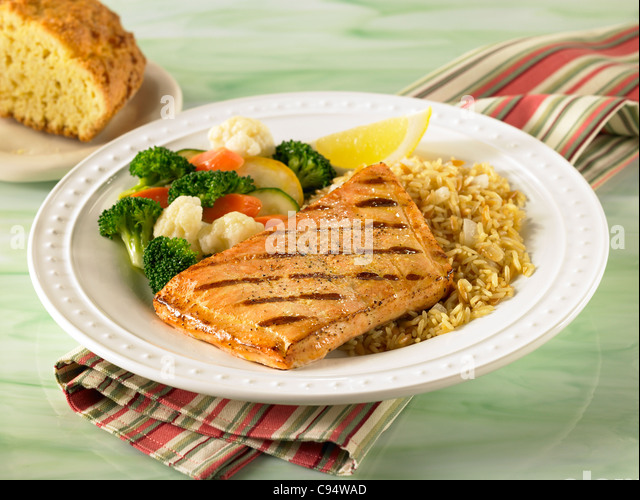 Salmon dinner served with rice and vegetables - Stock Image