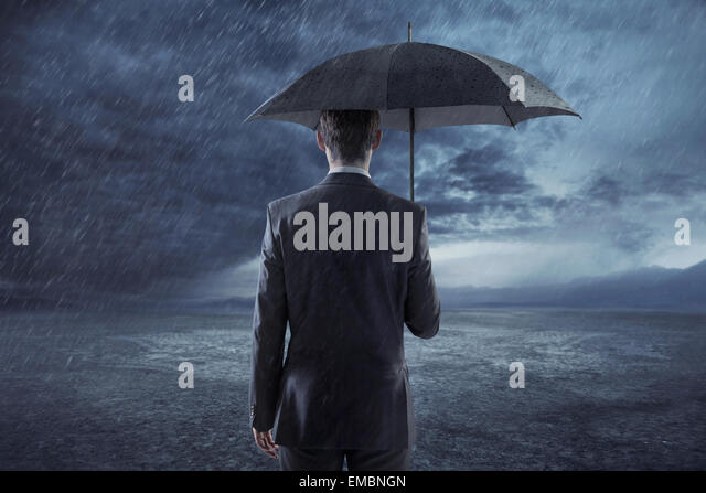 Depressed businessman standing with an umbrella - Stock Image