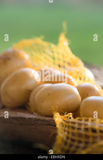 group of whole potatoes on rustic wood within carry net. - Stock-Bilder