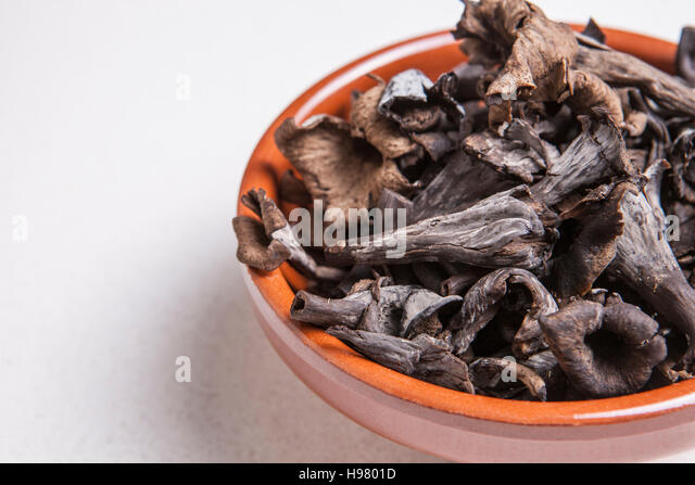 Clay bowl full of Horn of Plenty mushrooms. Isolated - Stock Image