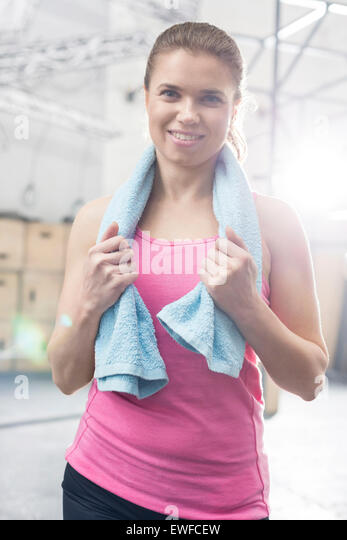 Portrait of happy woman with towel around neck standing in crossfit gym - Stock-Bilder