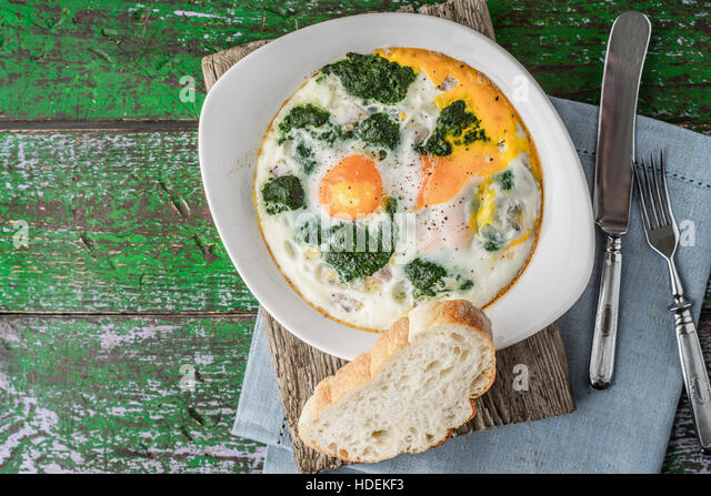 Florentine eggs with pureed spinach on the wooden table horizontal - Stock Image