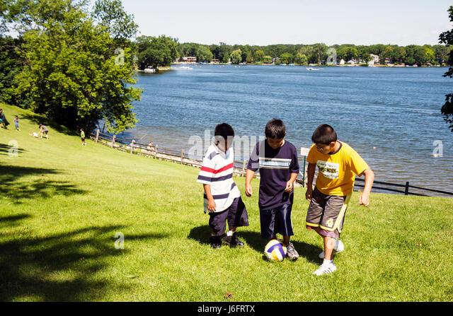 Wisconsin Kenosha Paddock Lake Old Settlers Park Hispanic boy play ball game sport summer vacation outdoor pals - Stock Image