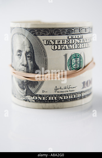 Roll of hundred dollar bills - Stock Image