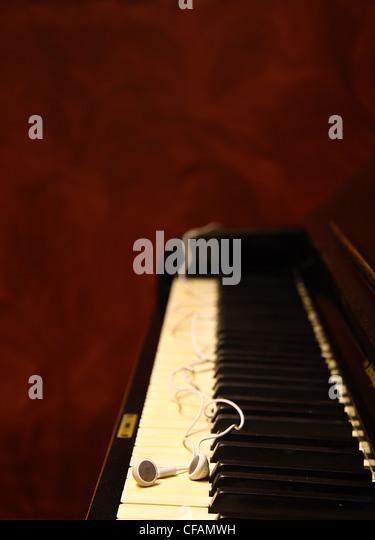 Earbuds resting on piano keys. - Stock-Bilder