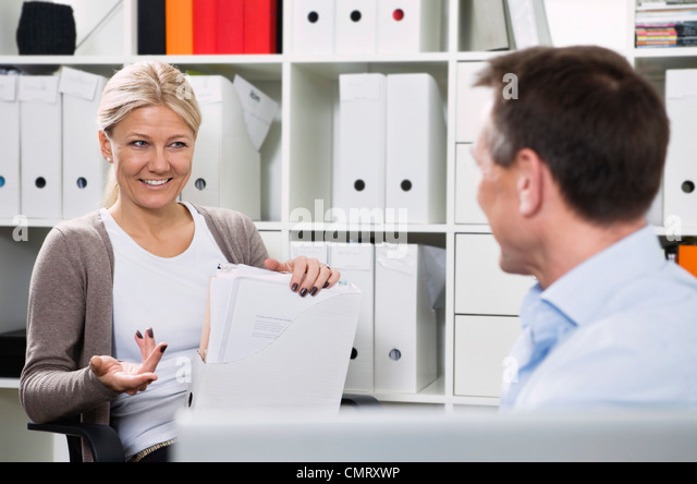 Colleagues talking at work - Stock Image