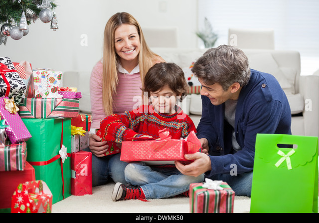 Woman With Boy And Man Opening Christmas Gift - Stock Image