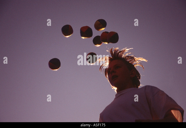 Boy 13 years old with juggling balls in air and hair flying Backlit  - Stock Image