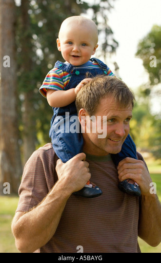 Father giving son ride on shoulders. - Stock Image