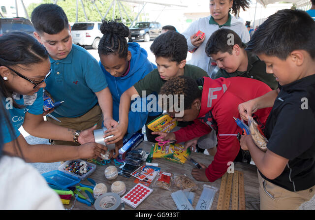 Middle school students design and build a science display out of cardboard and other simple recycled products on - Stock Image