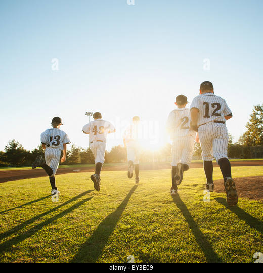Baseball players (10-11) running on baseball diamond - Stock Image