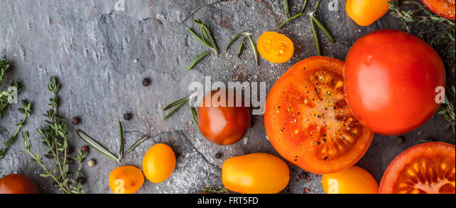 Tomatoes mix  with herbs on the stone table wide screen - Stock Image
