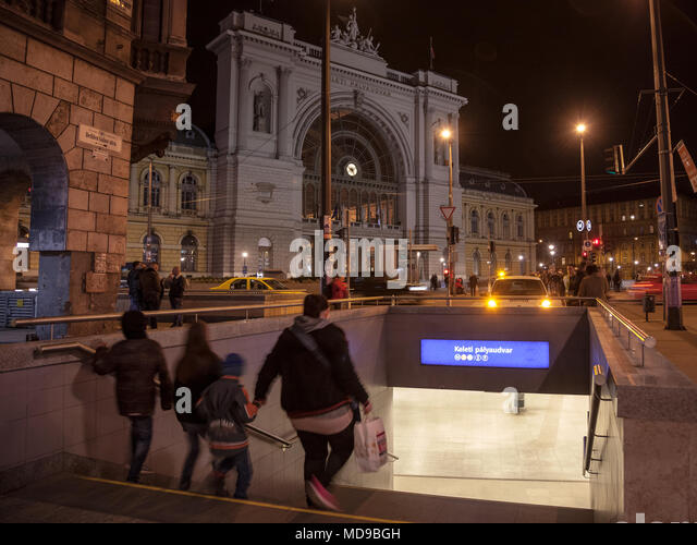 BUDAPEST, HUNGARY - APRIL 6, 2018: Family going down the stairs of a metro Station in front of Budapest Keleti Palyaudvar train station at night  Pict - Stock Image
