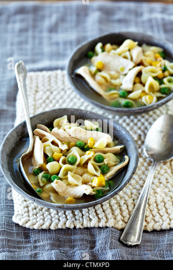 Chicken noodle soup with peas and sweetcorn - Stock Image